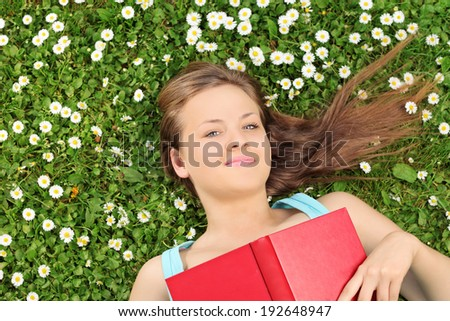 Beautiful girl lying in a meadow full of flowers and holding a book