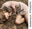 beautiful girl lying in the dry grass - stock photo