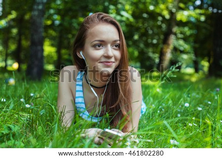 beautiful girl lying in the grass and listening to music