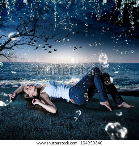 beautiful girl lying in the rain on a meadow in the evening - stock photo