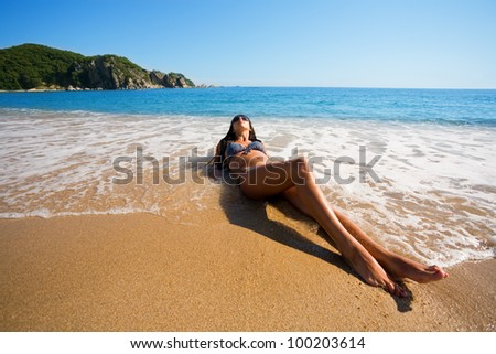 Beautiful girl lying in the surf - stock photo