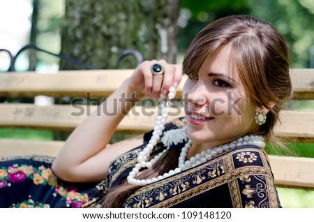 Beautiful girl lying on a bench - stock photo
