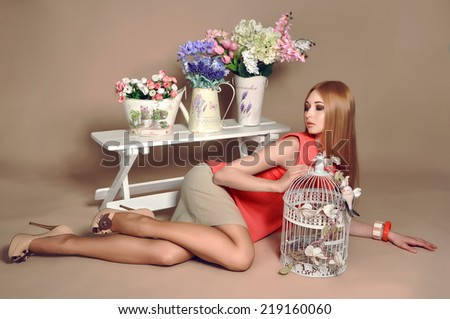 beautiful girl lying on a flow with a birdcage and flowers - stock photo