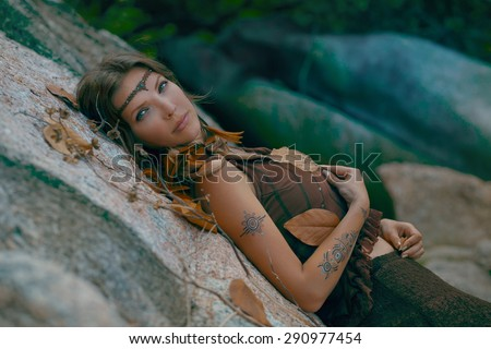 beautiful girl lying on a rock  - stock photo