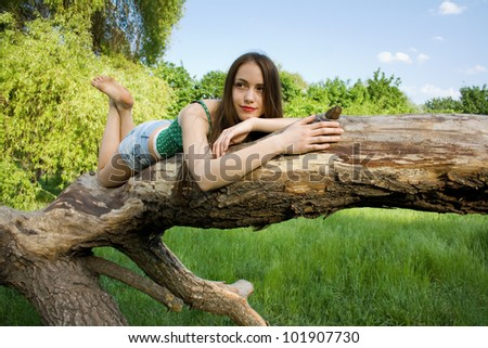 Beautiful girl lying on a tree in denim shorts and a t-shirt loo - stock photo