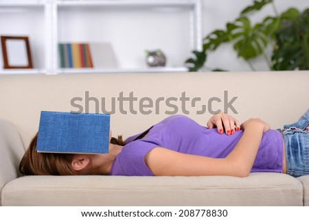 Beautiful girl lying on sofa and sleeping. young brunette covered face with book - stock photo