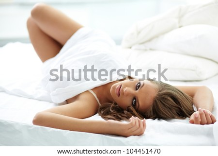 Beautiful girl lying on the bed in a sensual pose - stock photo