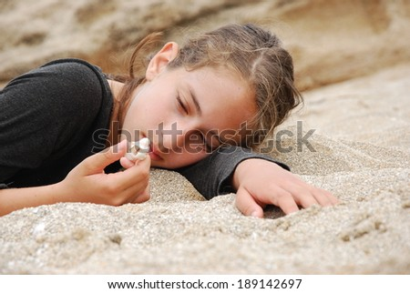 Beautiful girl lying on the sand and looking at seashell on her hand