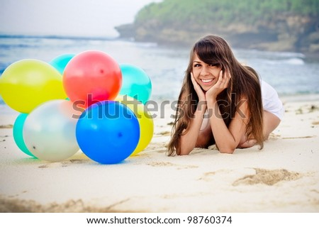 beautiful  girl lying with  bunch of colorful air balloons at the beach - stock photo