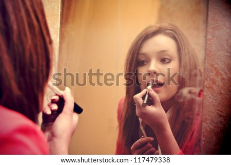 beautiful girl make up in front of the mirror, grunge background - stock photo