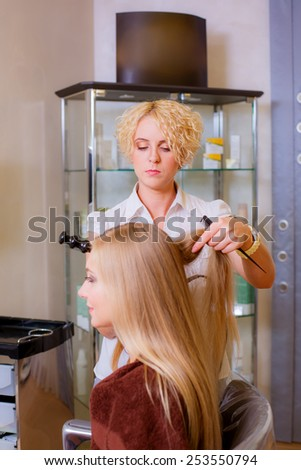 beautiful girl makes hair styling in a beauty salon - stock photo