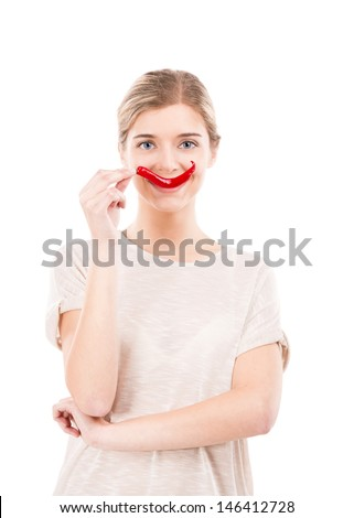 Beautiful girl making a smile with a red chilli pepper in front of the mouth, isolated over white background