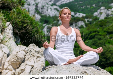 Beautiful girl meditating in yoga pose - stock photo