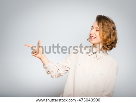 beautiful girl mocking of you, close-up, isolated on a gray background