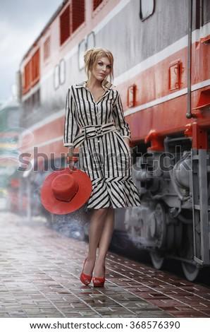 Beautiful girl model at the train station. Fashion, style, travel, beauty. - stock photo