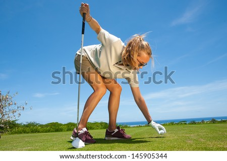beautiful girl model with long blond hair playing golf in a sunny summer day on the island of Mauritius. golf course is located on the shore of the ocean - stock photo