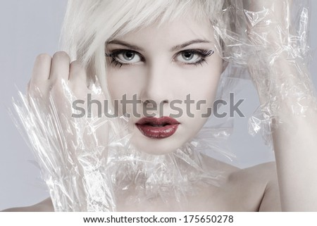 Beautiful girl model with plastic around her neck. Toned and professional makeup. - stock photo