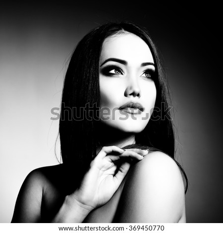 Beautiful girl. Natural beauty portrait. Young woman with beautiful healthy face and long brown hair looking at camera. Black and white. - stock photo
