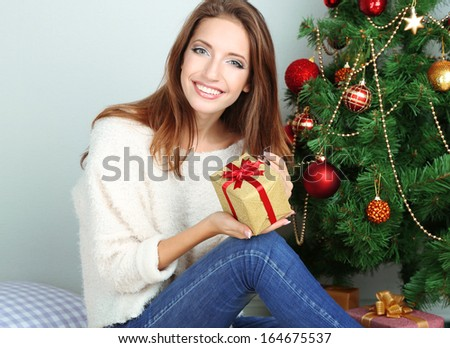 Beautiful girl near Christmas tree with gift