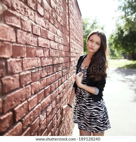 beautiful girl near red brick wall portrait - stock photo
