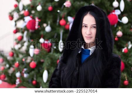 Beautiful girl near the Christmas tree - stock photo