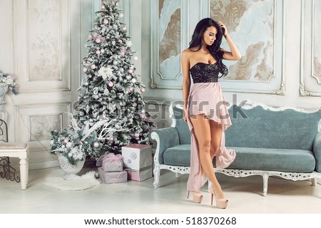 Beautiful girl near the Christmas tree! Girl in a smart dress at Christmas.