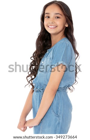 Beautiful girl of school age Eastern appearance with long , curly dark hair smiling. in denim overalls. Closeup - Isolated on white background - stock photo