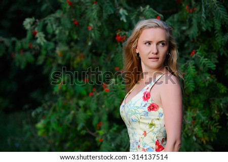 Beautiful girl on a background of a bush of a mountain ash - stock photo