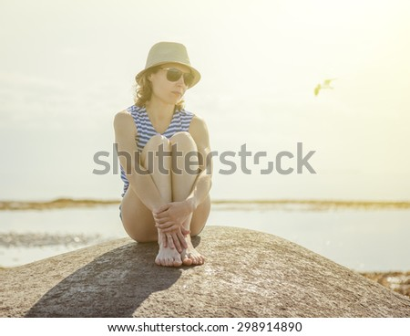 Beautiful girl on a beach in sunglasses and a hat. - stock photo