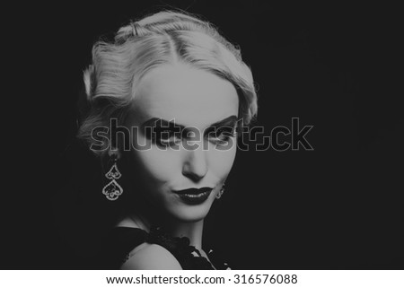 Beautiful girl on a dark background. Incredible dress and jewelry. Unsurpassed image of a beautiful girl. Black and white photo. Professional makeup.