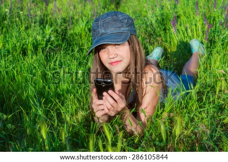 beautiful girl on a green meadow with phone in hand  - stock photo