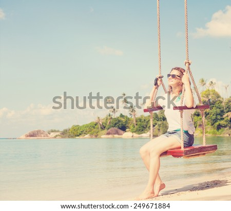 beautiful girl on a swing against the background of tropical seascape, retro toning - stock photo