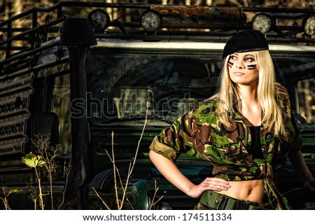 Beautiful girl on camouflage outfit, off-road vehicle behind - stock photo