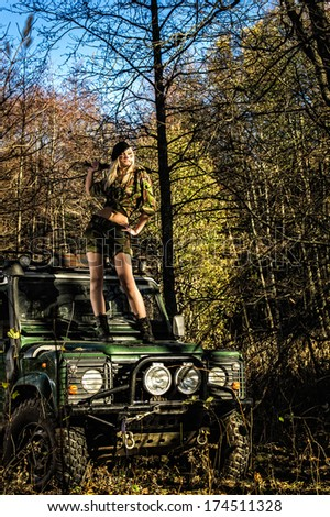 Beautiful girl on camouflage outfit with machete, she standing top of the off-road vehicle bonnet - stock photo