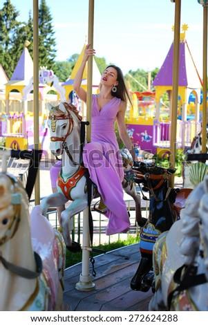 Beautiful girl on carousel amusement ride at the park. Fashion photo - stock photo