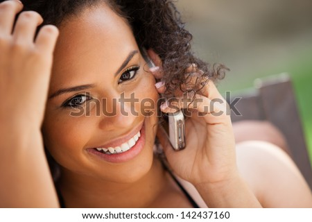 Beautiful Girl on her cell phone Smiling looking at camera - stock photo