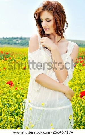 beautiful girl on rapeseed field in bloom - stock photo