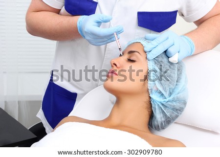 Beautiful girl on rejuvenation procedure in beauty clinic filler injection. Injection in her lips. - stock photo