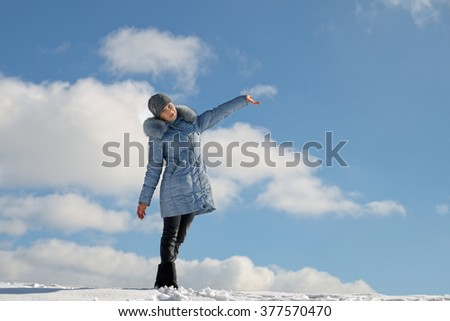 Beautiful girl on snowy hill, blue sky in the clouds.