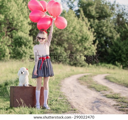 beautiful girl on suitcase with red balloons outdoor