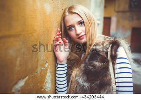 beautiful girl on the background of old wall - stock photo