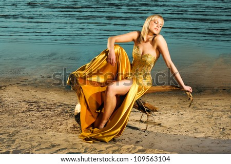 beautiful girl on the beach in a gold corset - stock photo