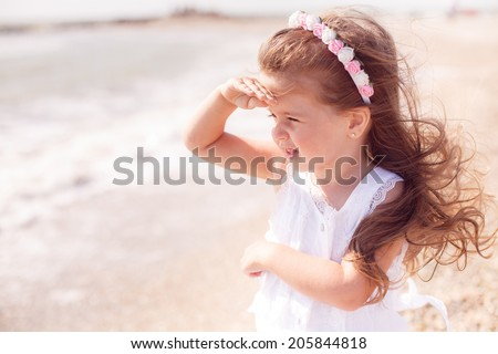 beautiful girl on the beach looking into the distance, wind, rest, happiness, closeup - stock photo