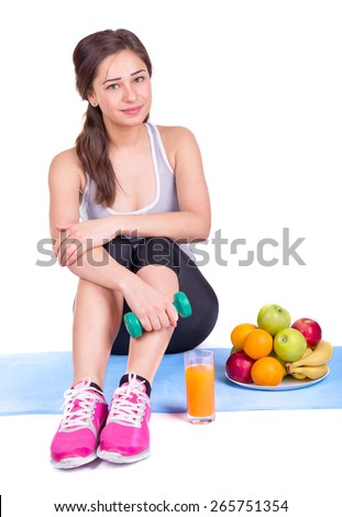beautiful girl on the carpet with dumbbell and fruit - stock photo