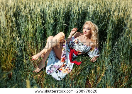 Beautiful girl on the field among the ears of corn. She flirts. Her mouth spikelet. - stock photo