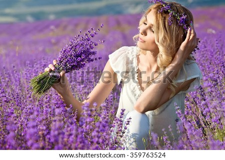 Beautiful girl on the lavender field.Beautiful blonde woman in the lavender field on sunset. Soft focus - stock photo