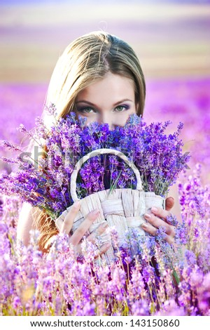 Beautiful girl on the lavender field. Young woman collects lavender in a basket - stock photo