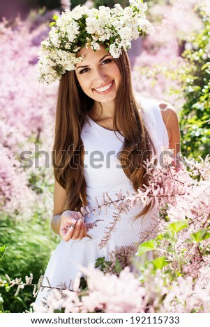 Beautiful girl on the nature in wreath of white flowers