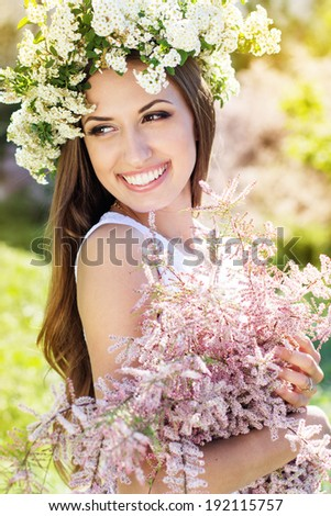 Beautiful girl on the nature in wreath of white flowers with bouquet of flowers