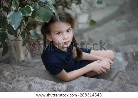 Beautiful girl on the old stairs of stone. A child with two pigtails. Schoolgirl.